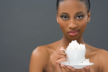 unfit: Woman holding a cup of sugar lumps