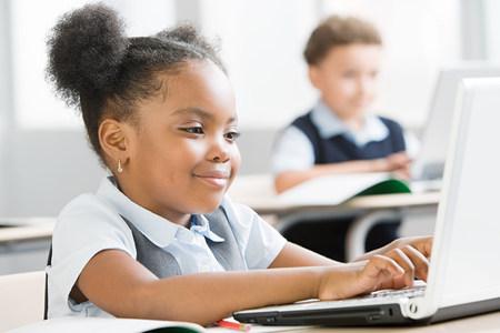 southern european descent: Schoolgirl using laptop