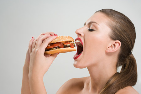 Young woman eating a burger LANG_EVOIMAGES