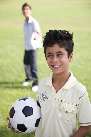 Portrait of a boy holding a football LANG_EVOIMAGES