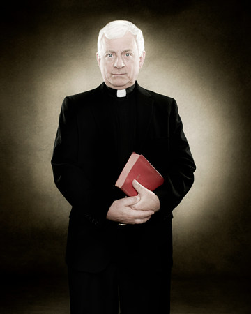 shadowed: Portrait of a priest holding a bible