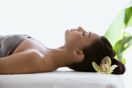 closed club: Young woman on massage table with orchid flower in hair