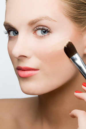 grooming product: Woman applying foundation LANG_EVOIMAGES