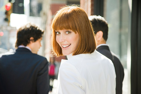 looking at viewer: Smiling ginger haired woman on the street