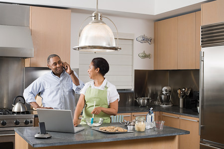 lap top: Couple in kitchen with laptop and cellphone