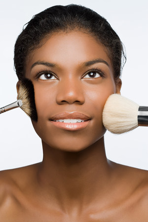 cropped shot: Woman with makeup brushes on face LANG_EVOIMAGES
