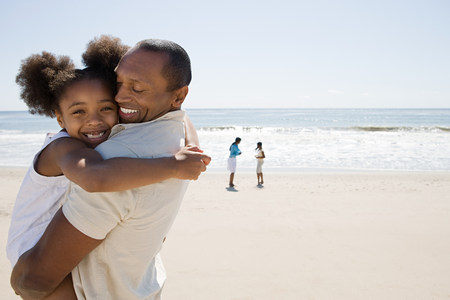 age 10 12 years: Father and daughter hugging on a beach LANG_EVOIMAGES