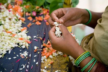 Woman making wreaths from jasmine flowers
