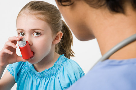 Girl taking asthma inhaler LANG_EVOIMAGES