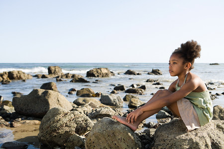 mixed age: Girl sitting on rocks at the beach
