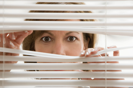 peep: Businesswoman looking through blinds LANG_EVOIMAGES