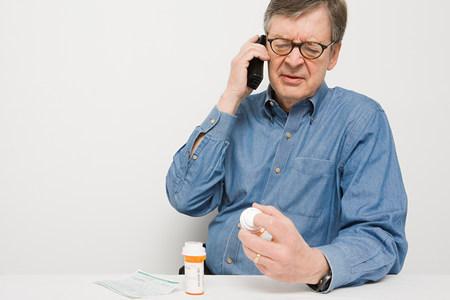 Man on telephone with medicine