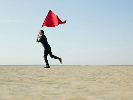dry suit: Businessman holding a red flag