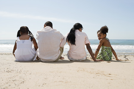 age 10 12 years: African american family sitting on a beach
