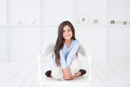 Portrait of a hispanic girl on a chair