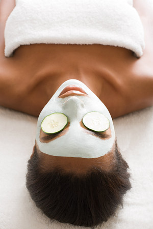 Woman wearing face mask and cucumber