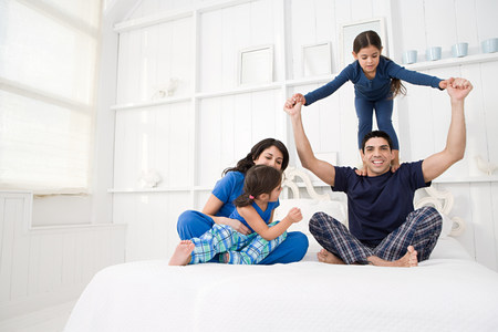 25 35: Hispanic family in a bedroom