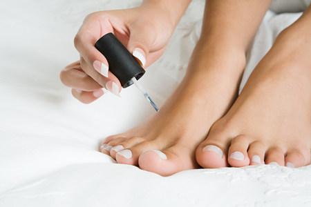 Woman painting toenails LANG_EVOIMAGES