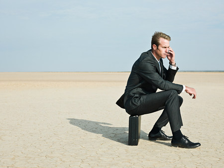 dry suit: Businessman sitting on a briefcase in the desert