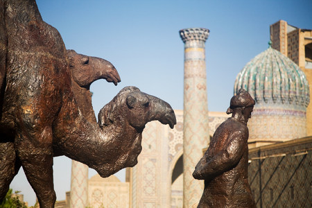 Statue of man leading camels outside mosque