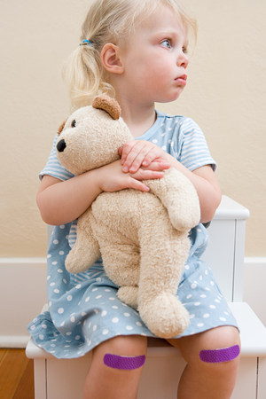 Girl with teddy bear and plasters on knees LANG_EVOIMAGES