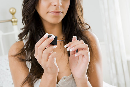 narcissist: Young woman painting fingernails