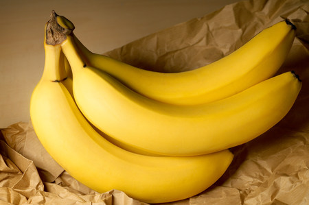 Bananas on brown paper bag LANG_EVOIMAGES