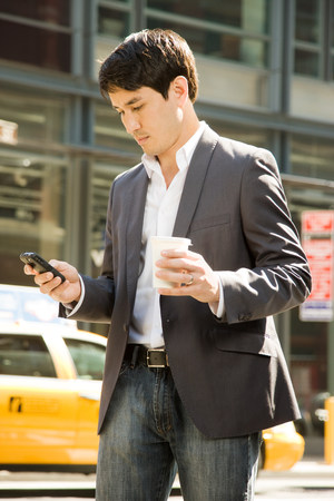 Male office worker using a cell phone on street