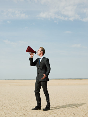 loudness: Businessman using a megaphone in the desert