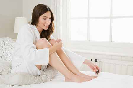 narcissist: Young woman painting toenails LANG_EVOIMAGES