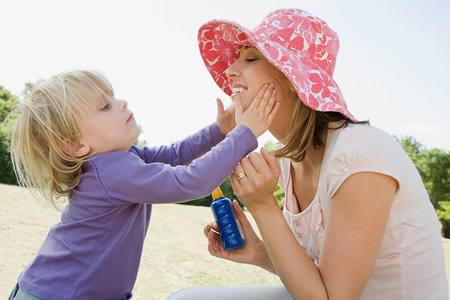 cremas faciales: Girl putting suncream on mother LANG_EVOIMAGES