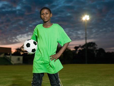 pubertad: Adolescente africano niño con el fútbol LANG_EVOIMAGES