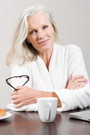 50 54 years: Middle aged woman sitting at breakfast table in bathrobe