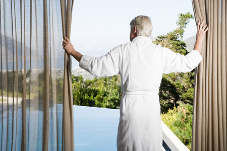 expect: Middle aged man wearing bathrobe pulling back curtains in front of swimming pool