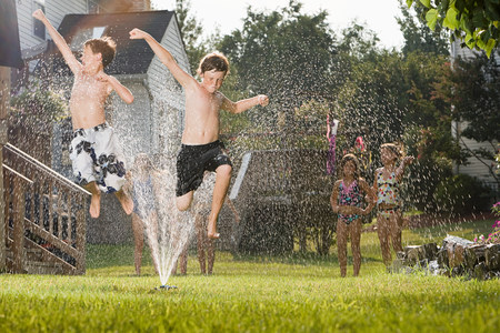 impulsive: Children jumping in sprinkler LANG_EVOIMAGES