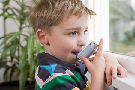 6 year old: Boy taking asthma inhaler