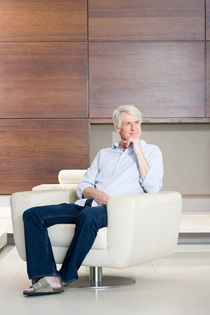 ponderous: Thoughtful middle aged man sitting on modern armchair