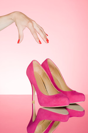 Hand reaching for pair of shoes