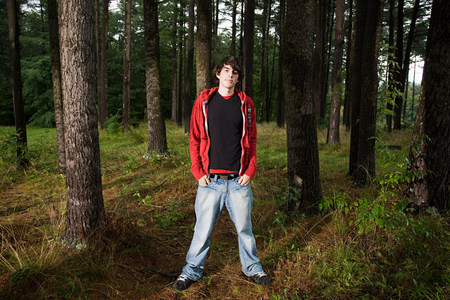 looking at viewer: Young man standing in forest