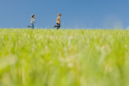 Boy and girl running in field