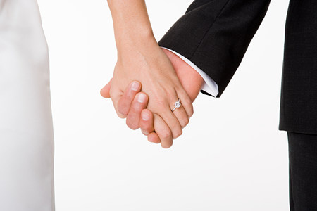 cropped shot: Newlywed couple holding hands