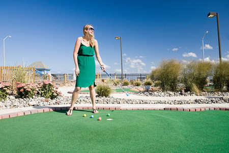 the americas: Woman playing miniature golf LANG_EVOIMAGES