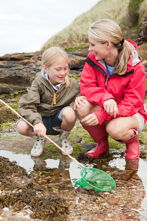 Mother and daughter by rock pools LANG_EVOIMAGES