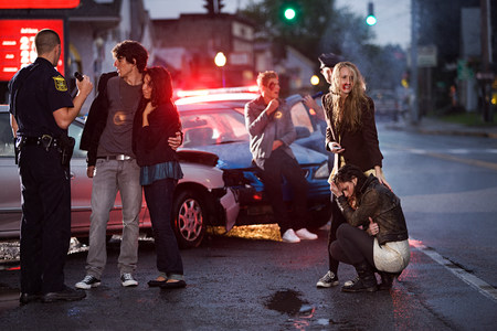 17 20: Young people and police officer at scene of car crash LANG_EVOIMAGES