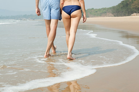 travel features: Legs of couple walking in sea