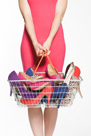 indecisive: Woman with with shopping basket full of shoes LANG_EVOIMAGES