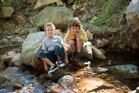 pastoral scenery: Boys sitting on rock by river LANG_EVOIMAGES