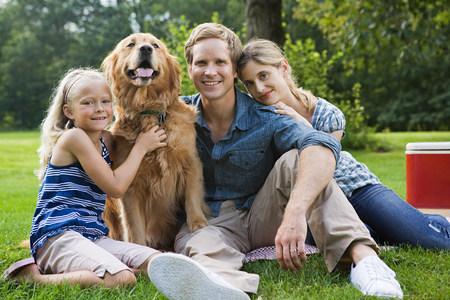 6 7 year old: Family in the park with golden retriever LANG_EVOIMAGES