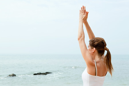 Woman practicing yoga by the ocean LANG_EVOIMAGES