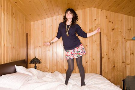 Log Out: Young woman dancing on bed LANG_EVOIMAGES
